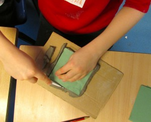 Cutting around templates to create ceramic tiles at the children's art school after school club
