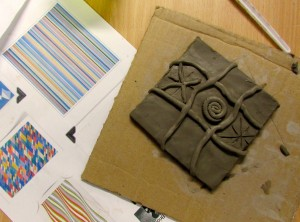 A relief pattern tile in progress at the children's art school after school club
