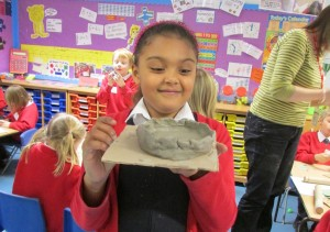 Girl showing her pinch pot bowl in progress at the Children's Art School after school art club