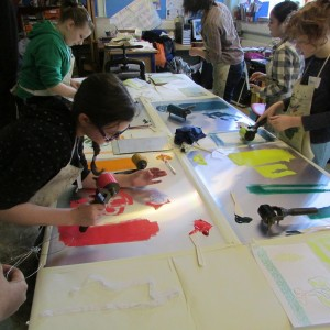 Inking objects at the printing table on the children's art school half term printing course led by artist, Chrys Allan