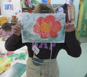 Girl showing her finished print at the half-term printmaking workshop at the Children's Art School with artist, Chrys Allen